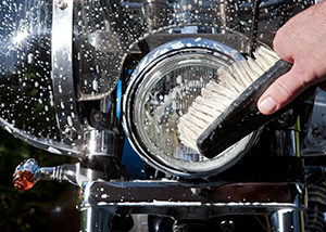 hand of biker washing headlight